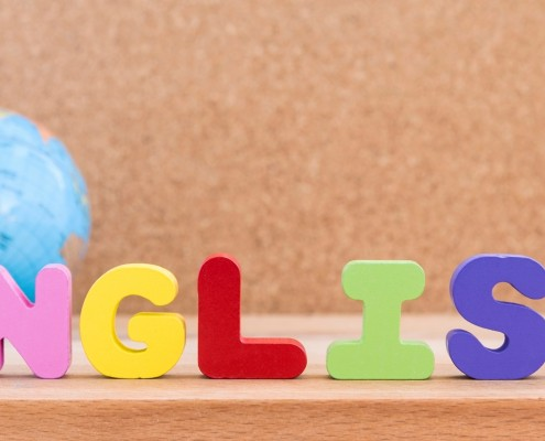 word english standing on the table with globe over wooden background with copy space, education concept